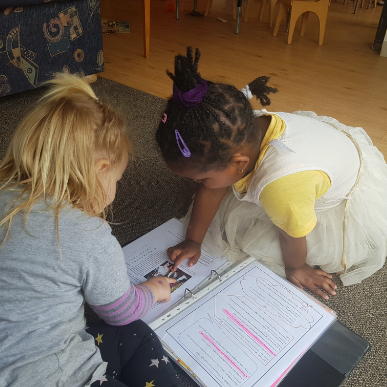 children looking at their portfolio-Gumdrops Early Learning Centre-Christchurch